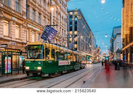 Helsinki, Finland - December 8, 2016: Tram Departs From A Stop On Aleksanterinkatu Street. Night View Of Aleksanterinkatu Street In Kluuvi District In Evening Or Night Illumination.
