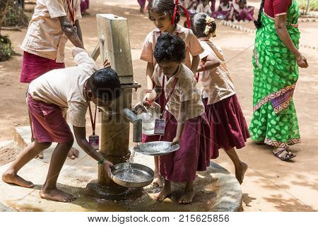 PONDICHERY PUDUCHERY INDIA - SEPTEMBER 04 2017. Unidentified boys girls children clean their plates before lunch at the outdoor canteen.