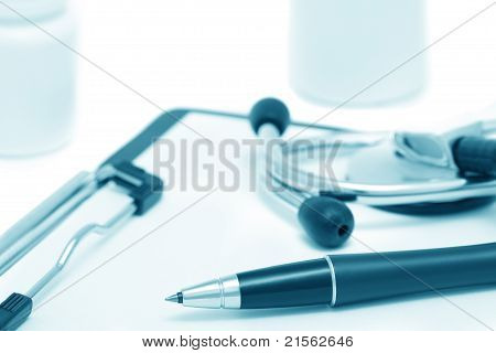 Clinic Still-life With Clipboard, Stethoscope And Tablets Jars (blue Toned)