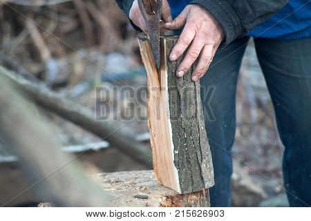 Close-up Of Men's Hands Chopping Firewood With An Ax.
