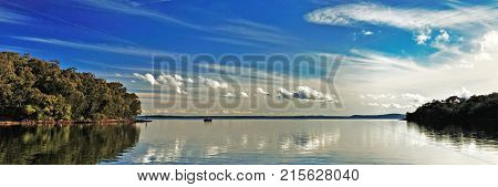 A spectacular inspirational brightly coloured cloudy sea water tropical panoramic seascape landscape featuring vibrant white Cirrus and Cumulus cloud in a vivid blue sky with water reflections. Port Stephens Australia.