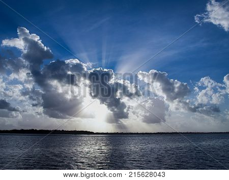 A spectacular inspirational brightly coloured cloudy sea water tropical seascape featuring a billowing white Cumulus cloud formation and clear Crepuscular Rays in a mid blue sky with ocean water reflections Australia.