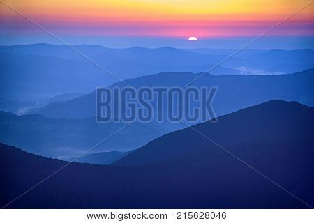 Amazing mountain landscape with colorful vivid sunrise on the bright sky over blue hills, natural outdoor travel background
