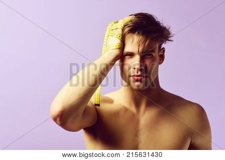 Guy With Naked Torso And Serious Face With Measuring Tape