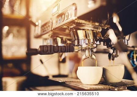 White cup standing beneath a coffeemaker, coffee pouring into it. Morning beverage preparation.