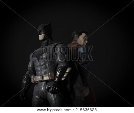 Studio image of Batman verses Superman action figures with dramatic lighting. Batman and Superman are DC Comics characters associated with the Justice League