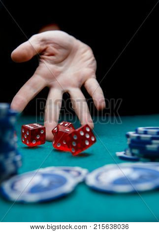 Photo of man throwing red dice on table with chips in casino