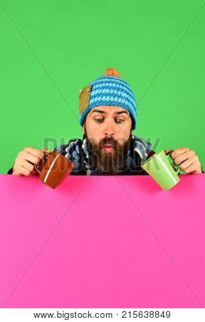 Hipster With Beard And Interested Face Has Tea Or Coffee