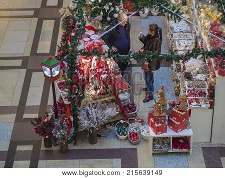 Czech republic Prague Palladium shopping centre November 23, 2017: man and woman shopping for christmas decoration in open stand store with colorful christmas balls light and gifts