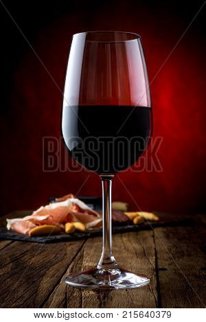 Glass of red wine and bord with ham serrano. Close up.