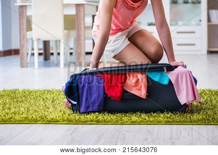 Woman trying to fit all clothing to suitcase before vacation