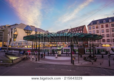 STRASBOURG FRANCE - November  23 2017: Busy center of the French city of Strasbourg Alsace with tramway and lots of commuters pedestrians walking under architectural station l'Homme de Fer