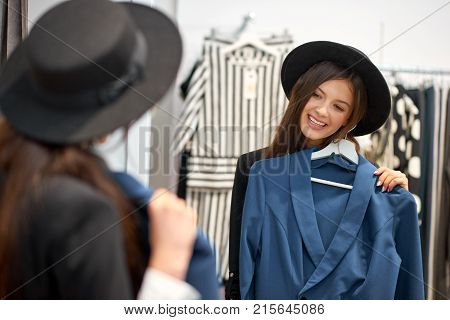 Attractive happy young woman smiling joyfully while trying on new clothes at the fashion store posing in front of the mirror copyspace lifestyle people positivity wellbeing consumerism concept. poster