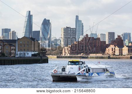 LONDON, UK - JANUARY 30, 2016: Skyline of the main office buildings in City of London with Thames Clipper ferry boat