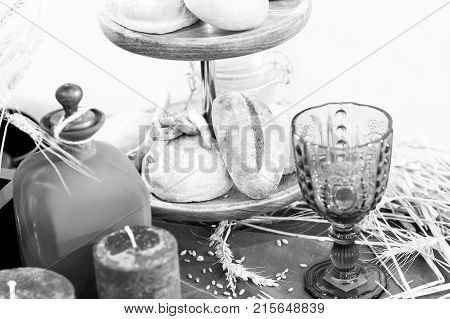 baked pasty or bread on wooden tray near glass bocal and candle with spikelet laying on table with nobody on christmas or easter celebration