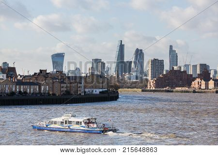 LONDON, UK - JANUARY 30, 2016: Skyline of the main office buildings in City of London with Thames Clipper ferry boat to Doubletree Hotel taken from  Canary Wharf