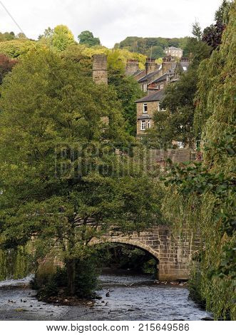 historic packhorse bridge in Hebden Bridge crossing the river with trees and surrounding houses