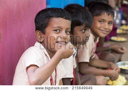PONDICHERY PUDUCHERY INDIA - SEPTEMBER 04 2017. Unidentified boys girls children sit on the floor with their plate of rice and egg at the lunch time in the outdoor canteen of the school.