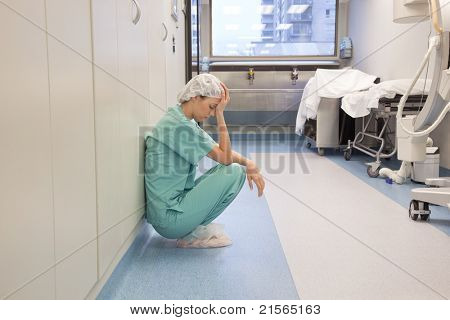 Tired doctor sitting alone in hallway