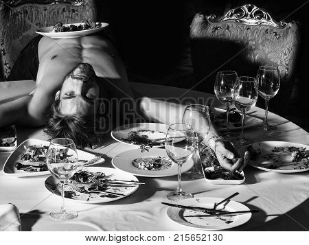 Handsome man or sexy muscular macho athlete bodybuilder with muscle torso undressed to waist lying on table with leftovers or residues food on dirty plates after banquet in restaurant