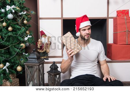 Christmas Macho In Santa Hat Sit At Fireplace