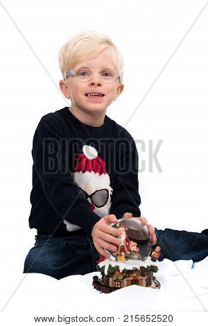 Waiting for Santa Claus: Handsome four year old boy with by Christmas music box and snow globe on white background