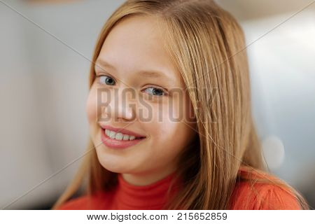 Beautiful face. Portrait of a joyful nice elated girl smiling and looking at you while being in a wonderful mood