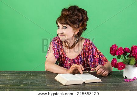 old lady or grandmother. Old woman reading book with glasses at flowers. Writer and poet granny read fairytale. Pension and retirement old age. Teacher or professor education teachers day.