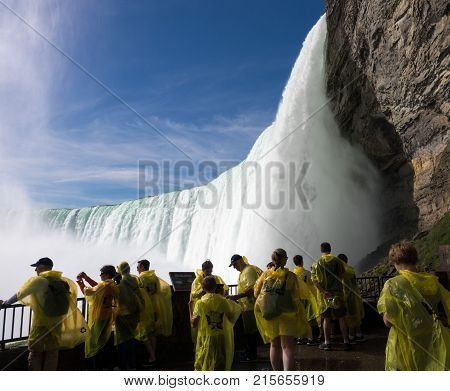 NIAGARA FALLS, CANADA - JUNE 30, 2016: Tourists at the Journey behind the Falls by the Canadian or Horseshoe waterfall  of Niagara Falls