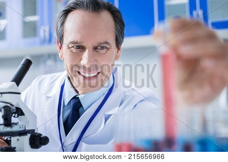 Rewarding job. Happy delighted nice scientist smiling and taking a test tube while feeling happy about his job