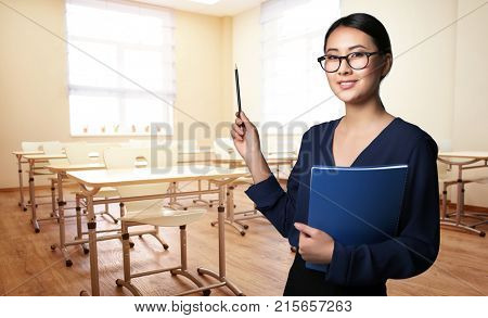 Portrait of young teacher in modern class room at school