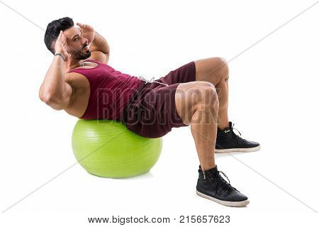 Attractive bodybuiler man exercising abs on an exercise ball in studio shot, isolatedo on white