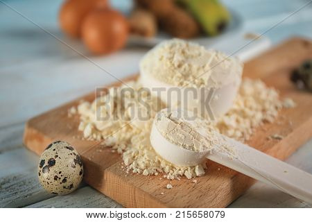 Measuring scoops with protein powder on wooden board