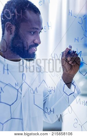 Behaviour of molecules. Positive intelligent handsome chemist standing in the lab and writing molecular formulas while doing theoretical research