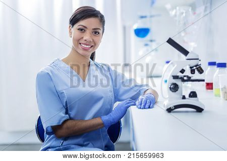 Female scientist. Happy cheerful nice woman looking at you and smiling while working as a scientist in the lab