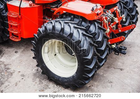 Big black rubber tire wheels of modern red tractor or combine or harvester, industrial machinery