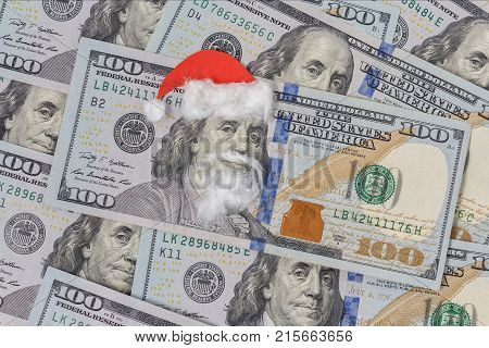 Benjamin Franklin in a Santa Claus hat on a bill. Christmas decorations