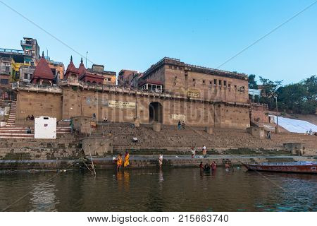 VARANASI INDIA - MARCH 15 2016: Wide angle picture of amazing architecture Raja Ghat in Ganges River during sunrise in Varanasi India.