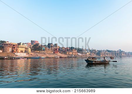 VARANASI INDIA - MARCH 15 2016: Wide angle picture from the boat of riverbank full of Ghats Temples and houses in Ganges River during sunrise in Varanasi India.