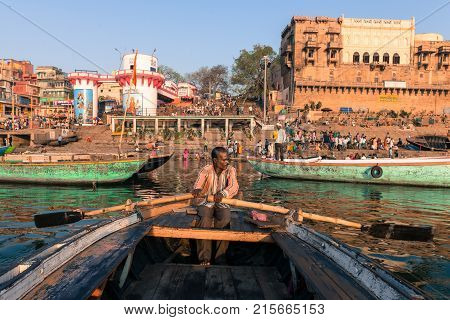 VARANASI INDIA - MARCH 15 2016: Horizontal picture of indian oarsman at the boat in front of Dashashwamedh Ghat inGanges River in Varanasi India.