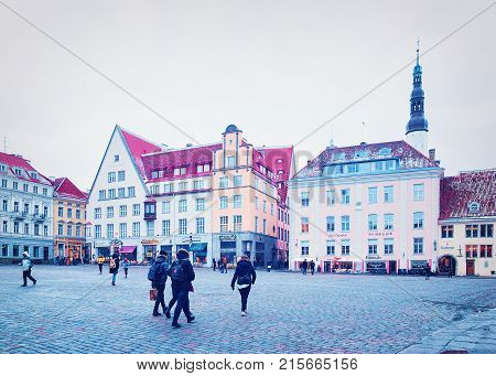 Tallinn Estonia - February 27 2017: People at Town Hall Square in the Old city of Tallinn Estonia in winter. Church of Holy Spirit on the background