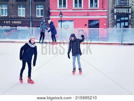 Tallinn Estonia - February 27 2017: Male teenagers ice skating on the rink at the Old town of Tallinn Estonia in winter