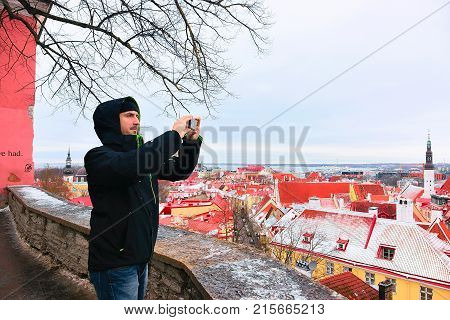 Tallinn Estonia - February 27 2017: Man with camera taking photos of Cityscape of the Old town of Tallinn Estonia in winter. View from Toompea hill