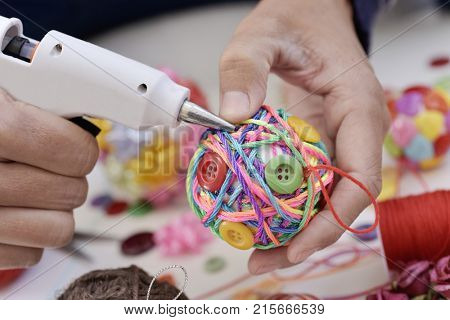 closeup of a young man making a handmade christmas ball using a hot glue gun with strings and buttons of different colors, and a pile of different haberdashery items
