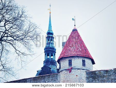 Defensive walls and Spire of St Nicholas Church at the Old town of Tallinn Estonia in winter