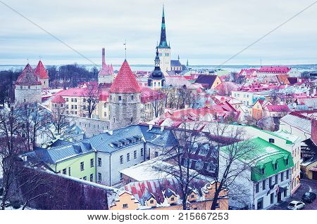Cityscape with St Olaf Church and defensive walls of the Old town of Tallinn Estonia in winter. View from Toompea hill
