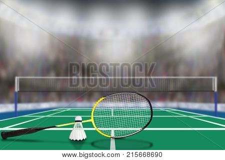 Low angle view of badminton racket and shuttlecock in arena with sports fans in the stands and copy space. Focus on foreground with deliberate shallow depth of field on background.