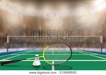 Low angle view of badminton racket and shuttlecock in arena with sports fans in the stands and copy space. Focus on foreground with deliberate shallow depth of field on background flash and lens flare.