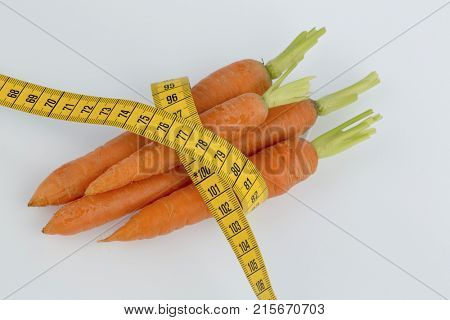 fresh carrots with measure tape