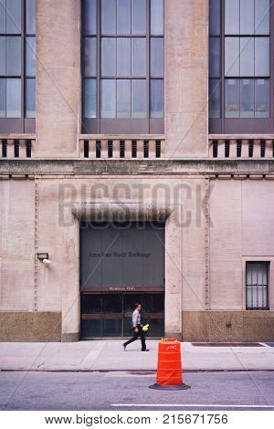 New York USA - May 5 2015: Man passing by Stock Exchange building on Wall Street in Lower Manhattan New York USA